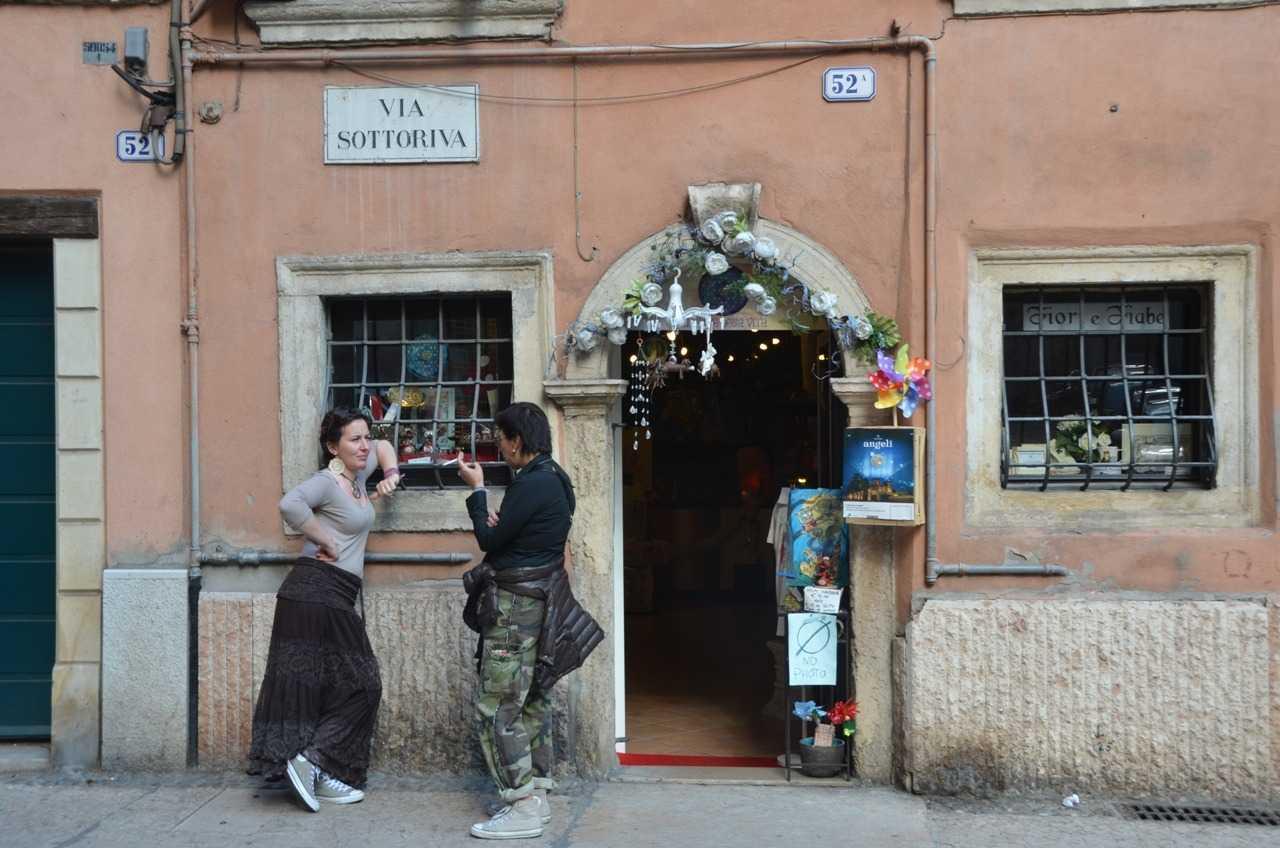 Adige Nehri kenarındaki Via Sottoriva'da arkadaşı ile çene çalan dükkân sahibi veya çalışanı…