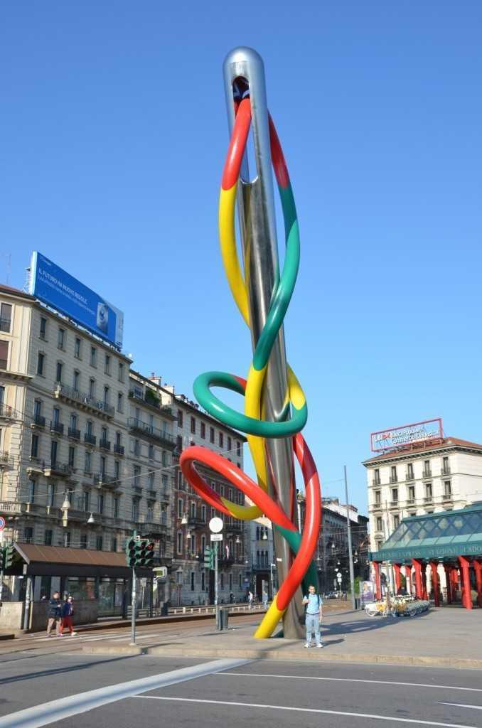 """Murat'ın yanında ufacık kaldığı, Piazza Cadorna'daki İsveçli Claes Oldenburg ve Hollandalı Coosje van Bruggen adlı sanatçıların eseri """"Needle, Thread, and Knot"""" adlı eseri - İğne-iplik 18 metre yüksekliğinde zımparalanmış paslanmaz çelik ve lif destekli plastikten yapılmış… Aynı meydandaki havuzda yer alan düğüm şeklindeki """"Knot"""" adlı eser ise 6 metre idi…"""