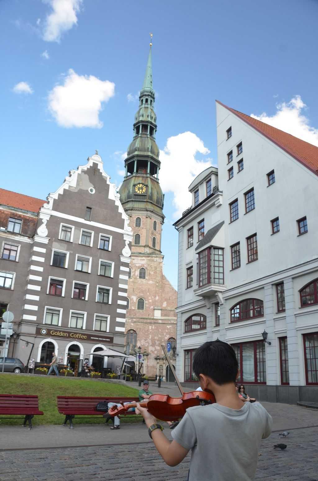St. Peter's Kilisesi önündeki Çinli kemancı çocuk - Riga